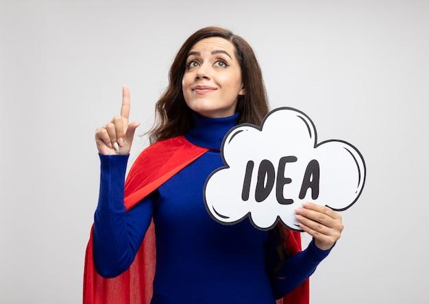 Довольная кавказская девушка-супергерой с красной накидкой держит пузырь идеи, глядя и указывая вверх изолированно на белой стене с копией пространства