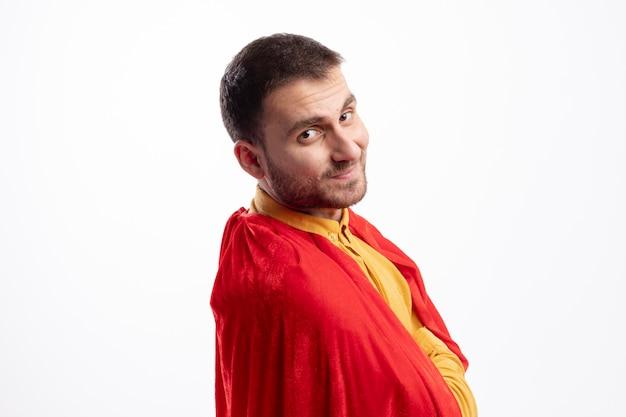 Довольный кавказский супергерой в красном плаще стоит боком со скрещенными руками и смотрит в камеру
