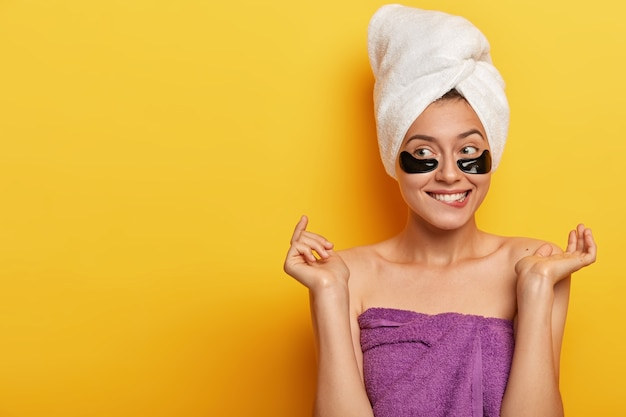 Pleased caucasian woman gets pleasure from beauty treatments, has problematic skin type, wears hydrogel patches under eyes, reduces impurities and puffiness, copy space on yellow wall