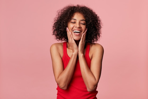 Pleased charming african american girl with afro hairstyle closed eyes in pleasure, touches her face with palms, laughs, rejoices from soft skin, wearing red singlet, isolated