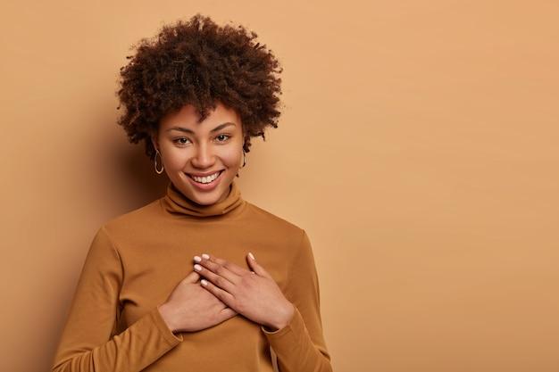 アフロの髪型で満足している魅力的な女性は素敵な贈り物を受け取り、心に手を押し、助けを感謝し、優しく微笑んで、とても感謝しています