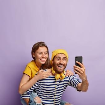 Piacevole coppia allegra fa selfie ritratto, ragazzo felice dà sulle spalle alla ragazza, sorriso ampiamente