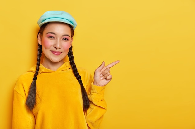 Pleased cheerful korean female model points aside, shows cool blank space, wears makeup, has two plaids, wears cap and yellow sweatshirt
