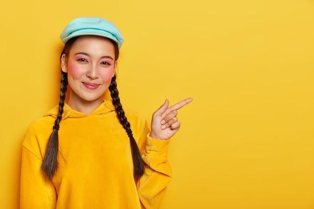 La soddisfatta modella coreana allegra indica da parte, mostra uno spazio vuoto fresco, si trucca, ha due quadri, indossa un berretto e una felpa gialla
