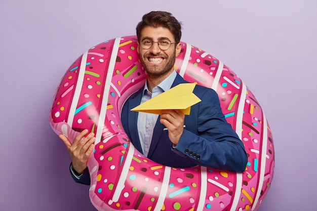 Pleased cheerful male director returns at work after summer holiday, throws paper plane, stands in inflated swimring, smiles positively