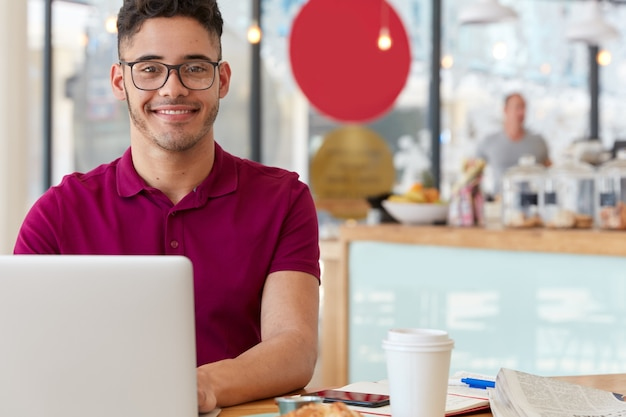 Pleased cheerful young man chats online with friends from abroad, sits in front of laptop computer, connected to 4g internet at coffee shop, wears optical glasses for good vision, likes his job