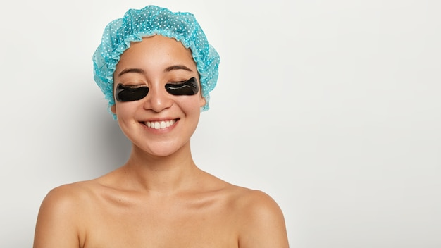 Pleased cheerful young woman has beauty undereye patch treatment, closes eyes from satisfaction, wears waterproof headgear, stands with naked body