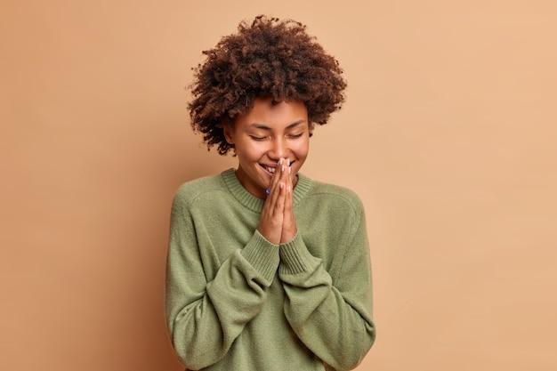 喜んで陽気な若い女性は、祈りのジェスチャーで手のひらを一緒に保ちます笑顔は積極的に目を閉じます茶色の壁に隔離されたカジュアルな長袖のジャンパーに身を包んだ巻き毛があります