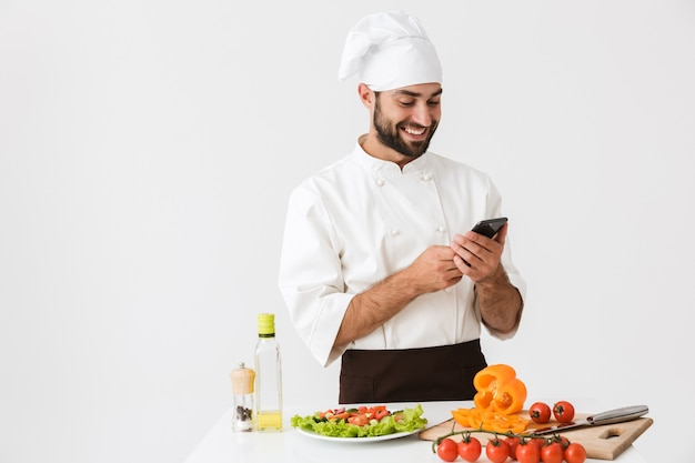 Pleased chef man in uniform smiling and holding smartphone while cooking vegetable salad isolated over white wall
