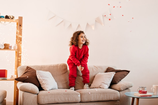 Pleased child jumping on couch. indoor shot of cute preteen girl standing on sofa.