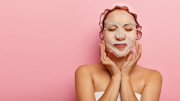 Pleased chinese woman enjoys cosmetic procedure, has natural paper face mask on cheeks, wrapped in towel, wears bathcap, has closed eyes, isolated on pink wall with free space for your advert