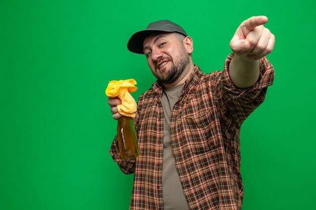 Uomo addetto alle pulizie contento che tiene in mano panni per la pulizia e detergente spray che punta a lato