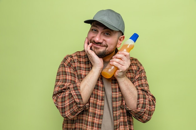 Uomo addetto alle pulizie contento che tiene in mano del detersivo per piatti