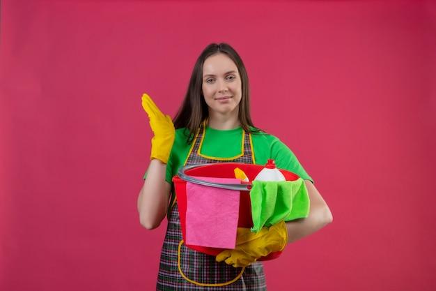Lieta pulizia giovane ragazza indossa uniformi in guanti tenendo gli strumenti di pulizia alzando la mano su sfondo rosa isolato
