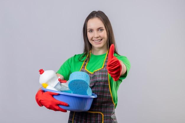 Lieta pulizia giovane ragazza indossa uniforme in guanti rossi che tengono gli strumenti di pulizia il suo pollice in alto su sfondo bianco isolato