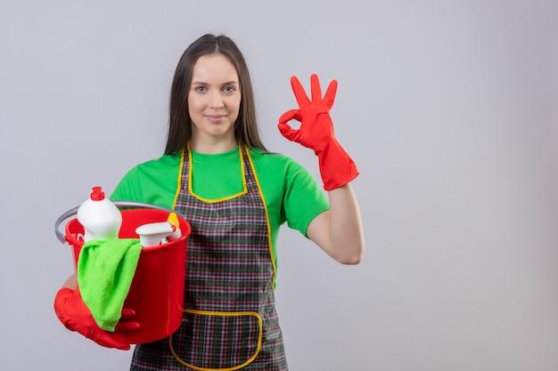 Felice pulizia giovane ragazza indossa uniforme in guanti rossi che tengono gli strumenti di pulizia che mostrano il gesto okey su sfondo bianco isolato