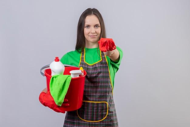 Lieta pulizia giovane ragazza indossa uniforme in guanti rossi che tengono gli strumenti di pulizia che mostra il gesto su sfondo bianco isolato