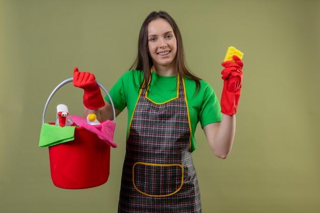 Lieta pulizia giovane ragazza indossa uniforme in guanti rossi che tengono gli strumenti di pulizia con spugna su sfondo verde isolato