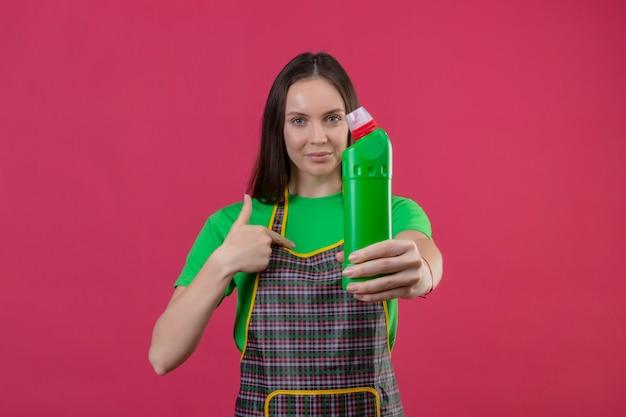 コメラに洗浄剤を差し出して制服を着た若い女性を喜んで掃除する孤立したピンクの壁に指を向ける