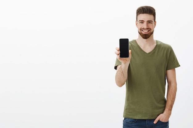 自信を持って見栄えの良いカリスマ的なひげを生やした男性がスマートフォンの画面を見せて幸せそうに笑う