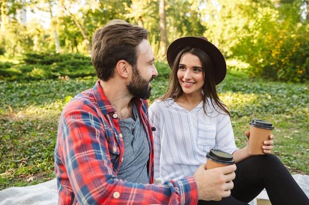 Довольная пара мужчина и женщина, одетые в повседневную одежду, пьют кофе на вынос во время отдыха в зеленом парке