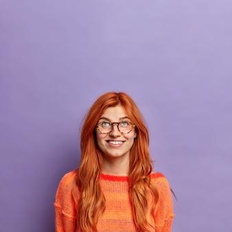 広い笑顔で上に集中している好奇心旺盛な赤毛のヨーロッパ人女性は、カジュアルな服装の光学メガネをかけています。