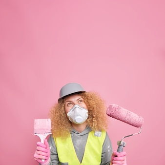 Pleased curly female builder or laborer wears helmet and protective respirator unform holds paint roller and brush focused above