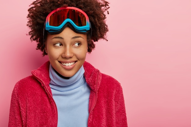 겨울 옷을 입고 기뻐하는 곱슬 여성은 이마에 스키 고글을 쓰고 기꺼이 옆으로 보이며 분홍색 벽 위에 모델이 있습니다.