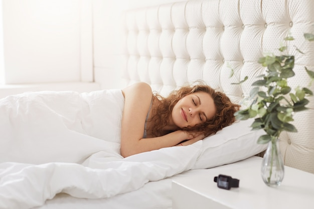 Pleased curly female has pleasant dreams, enjoys day off and good rest on comfortable bed in bedrooom, doesn`t want to get up early. young woman naps after work, enjoys calm domestic atmosphere