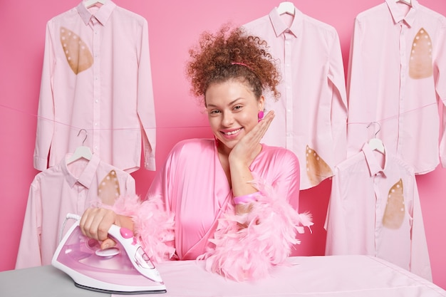 Pleased curly haired housewife dressed in gown strokes clothes poses near ironing board smile cheerfully does housekeeping chores poses against ironed shits on pink wall. daily chores.