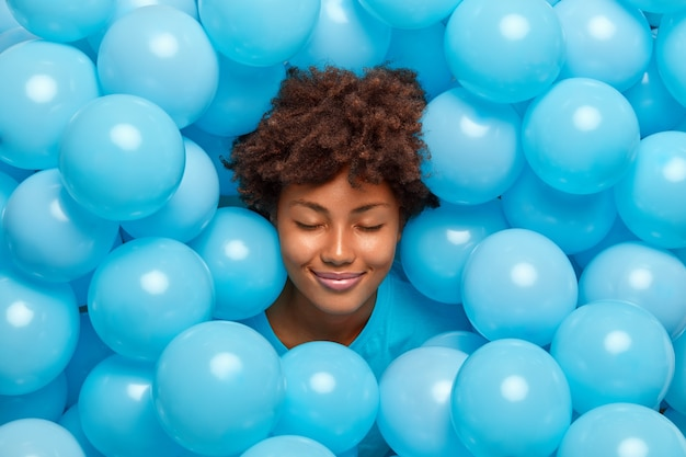 Pleased curly haired woman closes eyes surrounded by many blue inflated balloons has festive mood has fun on party feels very happy