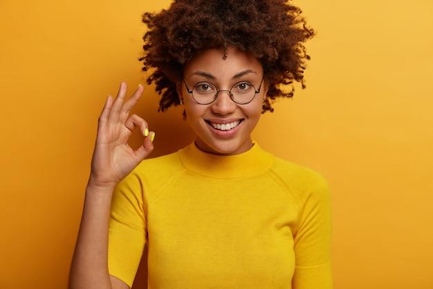 La donna dai capelli ricci soddisfatta fa un gesto di conferma, giudica qualcosa, dà approvazione, dice eccellente, indossa occhiali rotondi e maglietta, isolato su muro giallo, incoraggia a non arrendersi