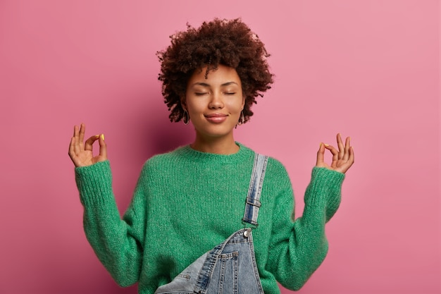 Pleased curly haired woman tries to calm down, unites with nature, raises hands and shows zen gesture, meditates or does yoga indoor, closes eyes, enjoys peaceful atmosphere for good relaxation