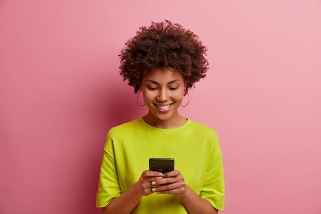 La donna dai capelli ricci soddisfatta digita messaggi in fretta, gioca a un nuovo gioco interessante, pubblica post online, naviga in internet, indossa una maglietta verde, posa contro il muro rosa, fa piani nel pianificatore mobile