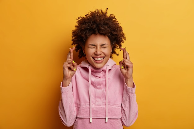 Pleased curly woman crosses fingers, wishes fortune before exam, has great hope for better, smiles positively, closes eyes, wears velvet sweatshirt, poses over yellow wall, puts all efforts in praying