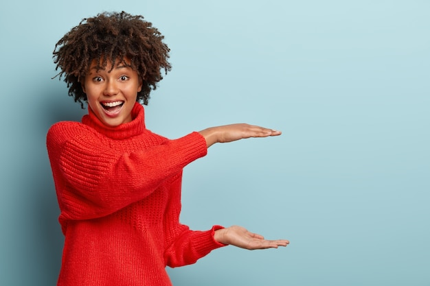 Pleased curly woman explains shape of box she needs, makes square with both hands over copy space, wears red jumper