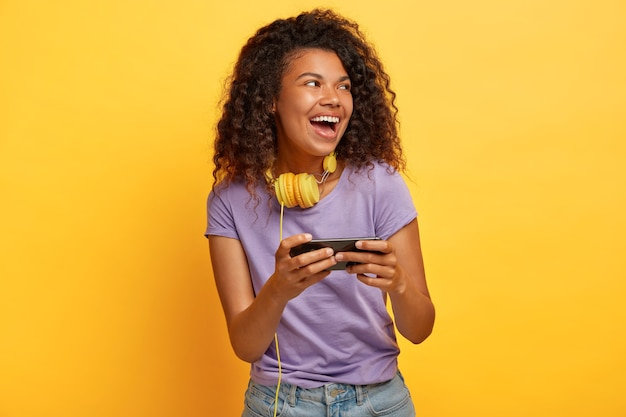 Pleased curly woman with afro haircut, holds smartphone horizontally, plays games online
