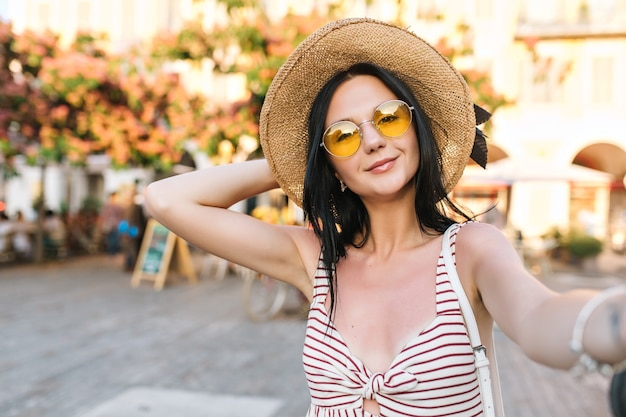 Довольная милая девушка в модных желтых очках проводит время возле ресторана на открытом воздухе, ожидая друзей и делая селфи