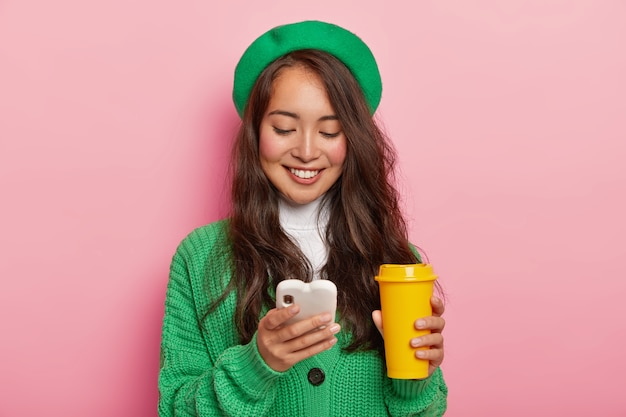 Pleased dark haired girl focused in cell phone, glad to get message of invitation for party, surfes social networks on modern gadget, checks newsfeed, wears green fashionable clothes, drinks coffee