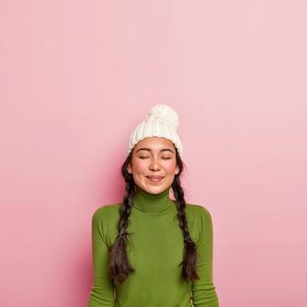 기뻐하는 검은 머리 소녀는 눈을 감고 친구와의 즐거운 만남을 생각하며 흰색 모자와 녹색 터틀넥을 착용하고 분홍색 벽에 서 있습니다.