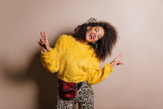 Довольная темноволосая женщина в желтом свитере танцует и смеется