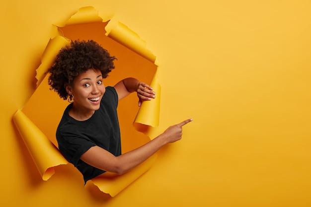 기쁘게 어두운 피부를 가진 아프리카 계 미국인 여성이 찢어진 공간에 서서 행복하게 웃고 종이 구멍에서 포즈를 취합니다.