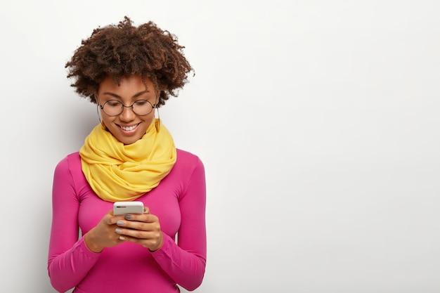 満足している暗い肌の女性は、現代の携帯電話を持ち、ディスプレイに焦点を当て、ピンクのタートルネックを着ています