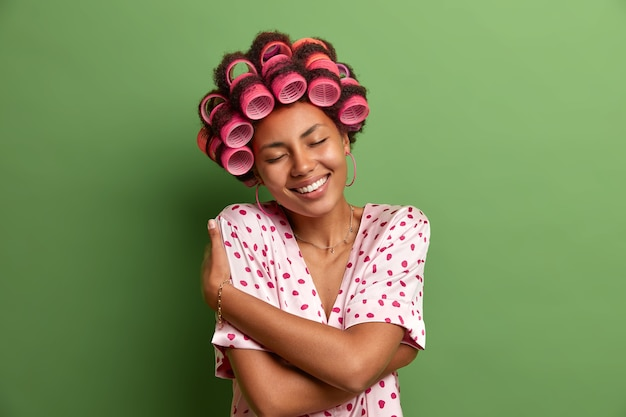Pleased dark skinned female model embraces herself, enjoys wearing soft pajama, tilts head and smiles pleasantly, wears hair rollers for making perfect hairstyle, isolated on green