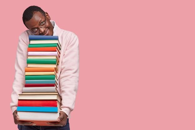 기뻐하는 어두운 피부의 힙 스터 학생이 무거운 책 더미에 기대어 캐주얼 스웨터를 입습니다.