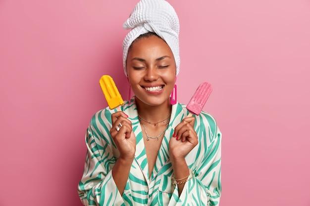 기뻐하는 짙은 피부의 여성이 입술을 물고, 맛있는 식욕을 돋우는 아이스크림을 들고, 냉동 디저트의 즐거운 맛을 상상하고, 머리에 수건을 감싸고, 가운을 입고,