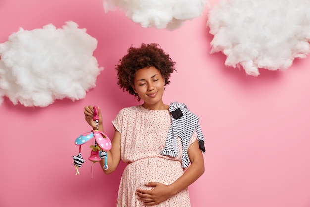 妊娠中の腹を愛撫する満足のいく浅黒い肌の女性は、生まれたばかりの子供が目を閉じて落ち着いて立っているのを感じ、妊娠を楽しんでいます。