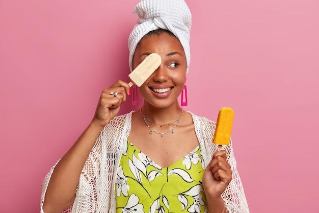 기쁘게 어두운 피부를 가진 여자는 눈 미소에 맛있는 아이스크림으로 눈을 덮습니다.