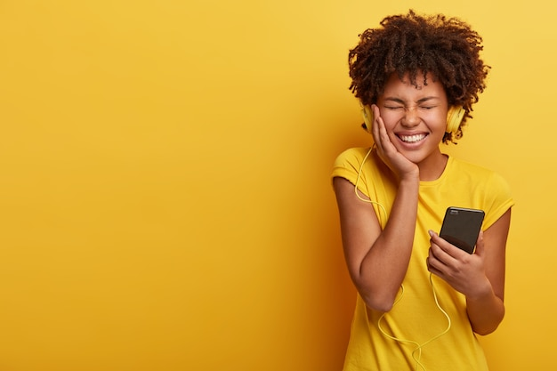 Pleased dark skinned woman feels great and happy, smiles broadly, holds smartphone connected to headphones, closes eyes from pleasure