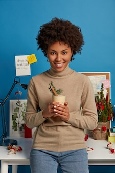 Pleased dark skinned woman holds homemade cocktail, dressed casually, has cheerful face expression enjoys winter time and tasty eggnog leans at white desk with small christmas tree